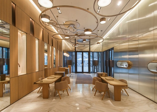 """Spanish designer Patricia Urquiola has designed the first US flagship storefor Italian watch brand Panerai in Miami's Design District, featuring a chandelier with shapes based on watch parts. The two-level, 2,200-square-foot (204 square metres) shop is outfitted with luxurious materials like marble and bronze and is located on the south-west corner of the district's Palm Court. The rectangular ground floor is lined with striated wood paneling with illuminated niche display cases. A sculptural chandelier of circles and gears runs the length of the space and was inspired by the inner workings of watches. """"In the boutique we have introduced some new features like the tailor made chandelier that evokes the precision mechanisms of a watch,"""" said Urquiola. The designer also recently redesigned the New York showroom for the Italian furniture brand Cassina, for which she is art director. Urquiola designed the furnishings for the Panerai store, including seating, tables, and service counters. The staircase at the rear of the shop has the same gold finish as the chandelier, and the profile of the open tread stair also resembles the teeth of a gear. A second floor viewing lounge is reserved for VIP customers and will also host private events including art exhibitions. A large wall clock looks like one of the company's watch faces. A model boat is meant to evoke's the company's history as a supplier of naval instruments for the Italian military. Long acquainted with the Florida city, Urquiola sees the boutique as the latest example of Miami's development as an international capital of design and culture. """"Miami is special to me because it is part of my family. As my sister and her family have been living there for more then 30 years,"""" she said. """"I see a new Miami now, a Miami 3.0, with the same values as before but with more attention to quality and internalization."""" """"The Design District is one of the better examples of this process, bound to the world of art and design, also b"""