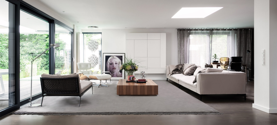 A living room of a private residence in Munich with a big white sofa, a brown center table, a white reclaimed chair, a lamp and a paint on the wall.  kitzig design studios Kitzig Design Studios- From Germany to the World Interior INTERNET Wohnraeume Bungalow Muensterland 02 1