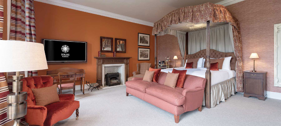 A bedroom in SCHLOSS Roxburghe, decorated in shades of pink and orange. The room has a big bed, a pink sofa and a orange/red armchair. kitzig design studios Kitzig Design Studios- From Germany to the World Schloss Roxburghe SZ 01 2