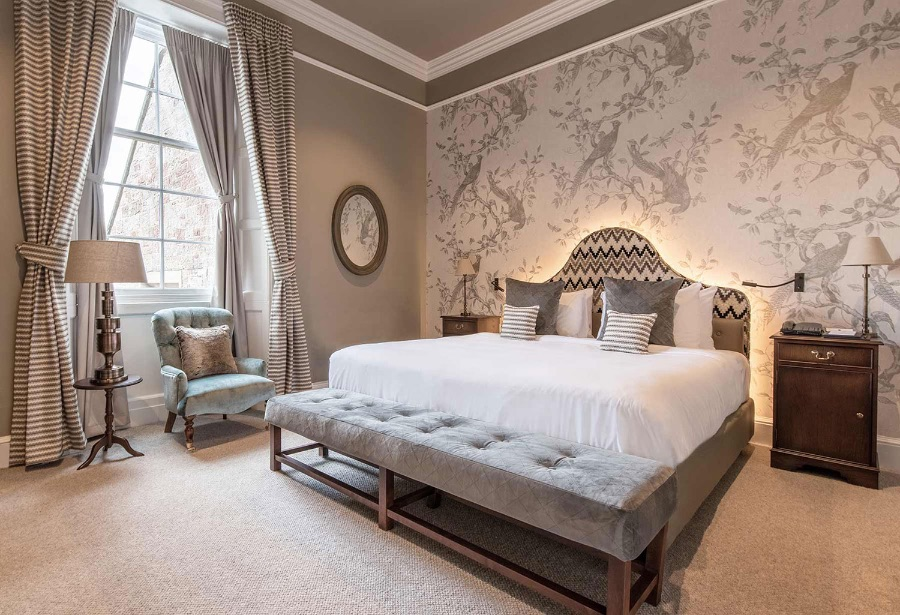 SCHLOSS Roxburghe bedroom, this one decorated in more neutral, smooth tones, featuring a baby blue armchair, and a grey sofa. kitzig design studios Kitzig Design Studios- From Germany to the World Schloss Roxburghe SZ 13 1 1
