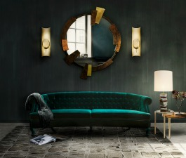 A green emerald sofa with capitoné in a modern home décor. This fierce living room set counts as well with the gold from the wall lamps and round mirror to contrast with the other pieces.