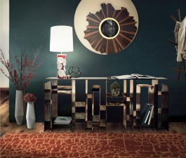 A mid century modern living room décor with a geometric console table with storage, a large wall mirror, a contemporary table lamp and an orange patterned rug.