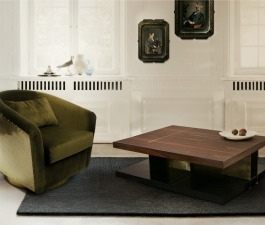 A velvet armchair and a rectangular coffee table are the attention focus of a mid century modern living room décor.